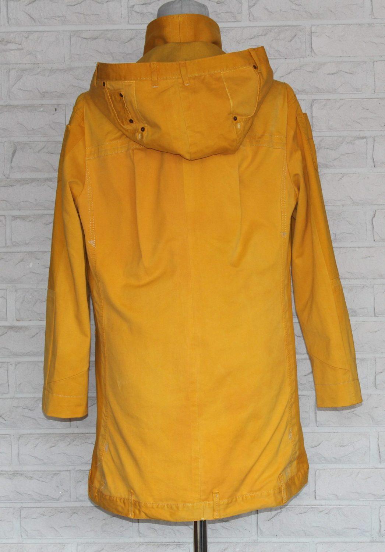 Keltainen takki irroitettavalla hupulla.